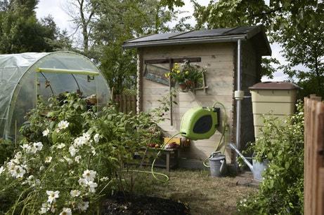 Un jardin potager avec sa serre de culture et son abri de jardin
