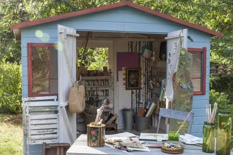 Un abri de jardin en bois avec plein de rangements au jardin