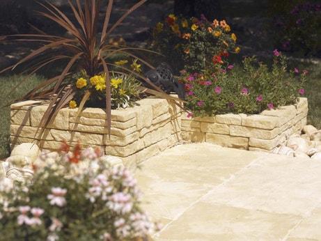 Un muret en pierre avec des plantes dans le jardin