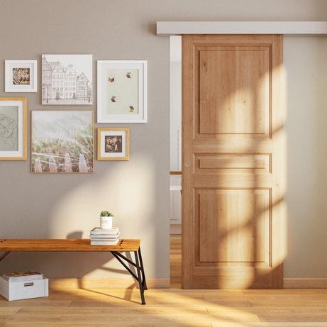Une porte coulissante en chêne rustique pour une entrée bien conçue