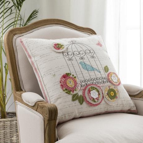 Un coussin imprimé aux motifs oiseaux pour un salon au style romantique