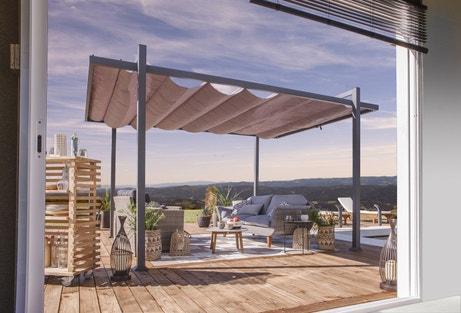 Un damier bicolore de dalles dessine un tapis dans la terrasse en lames de bois.