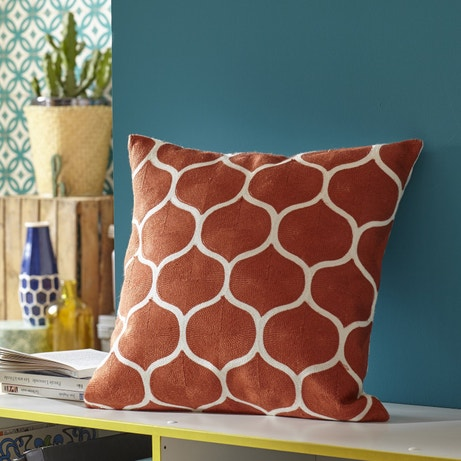Un coussin brodé orange avec motifs