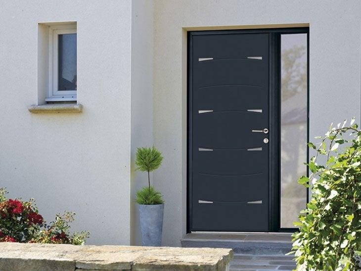 Les inserts inox sur la face extérieure de la porte Nodus lui confèrent un design contemporain. Cette porte en aluminium se décline en différents coloris et en finition sablée ou mate.