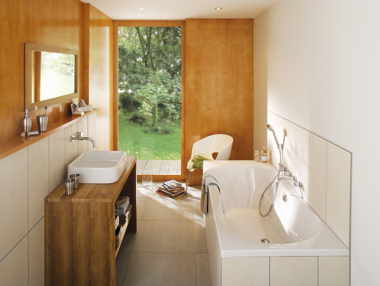 Une salle de bains aux tons orange ouverte sur le jardin ...