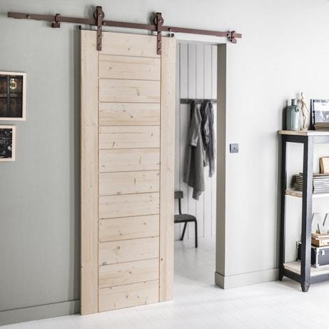 Une porte coulissante en bois brut avec le système coulissant, le tout en mode industriel