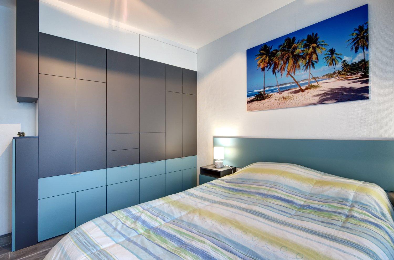 Tout un mur de rangement noir et bleu dans la chambre de ...