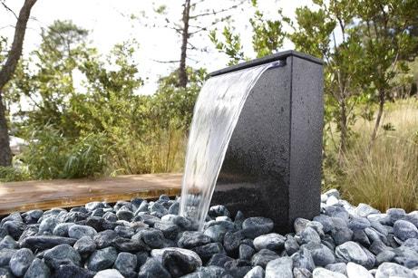 Une fontaine de jardin avec des galets gris pour une déco contemporaine