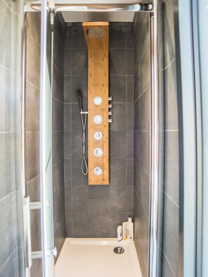 effet styl avec une colonne de douche en bois et un carrelage effet b ton dans la douche de. Black Bedroom Furniture Sets. Home Design Ideas