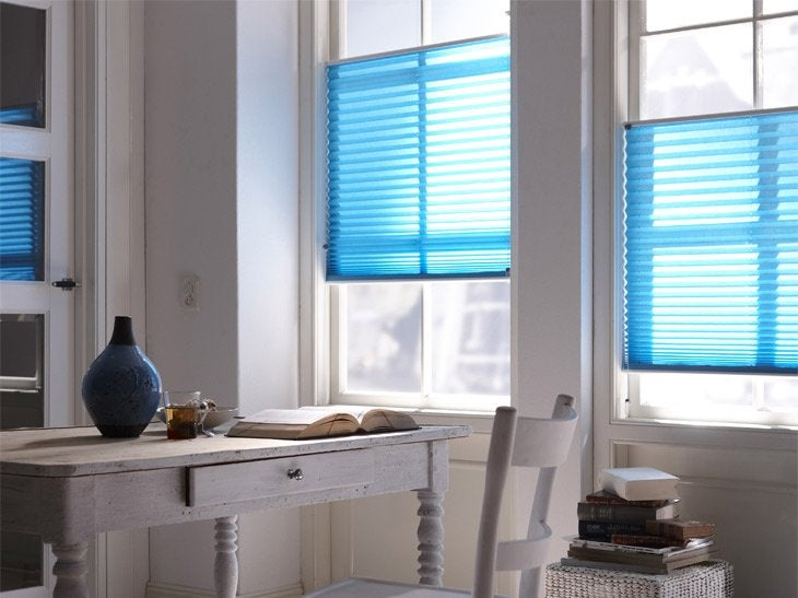 Des stores colorés, placés à différents niveaux, permettent de donner une autre dimension à la pièce.