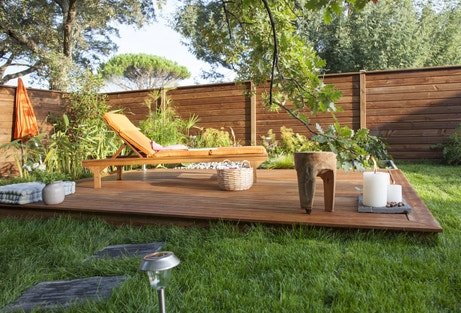 Terrasse en bois au mileu du jardin avec bain de soleil en bois