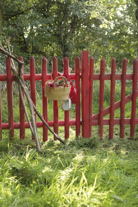 Une barrière rouge en bois pour cloisonner votre jardin