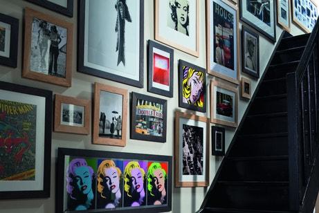 Un mur rempli de cadres divers qui habillent la cage d'escalier