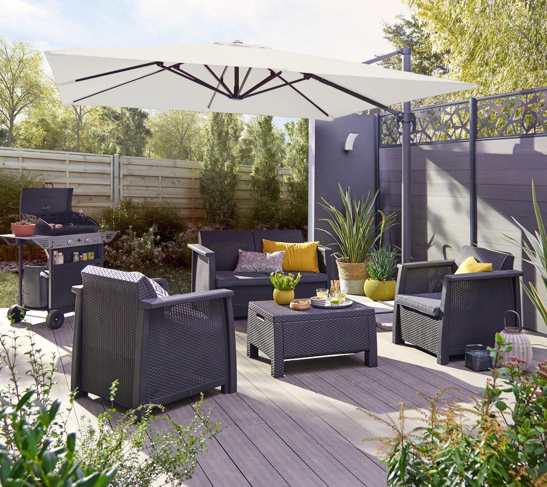 Une terrasse composite, un parasol et un salon de jardin bas pour ...