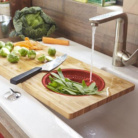 Une planche à découper avec un égouttoir en bambou rouge