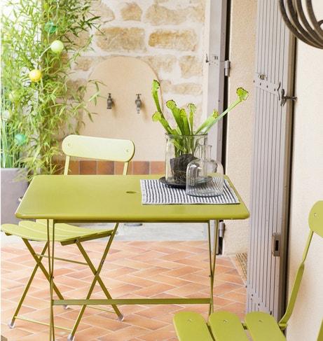 Un salon de jardin vert avec table et chaises en métal