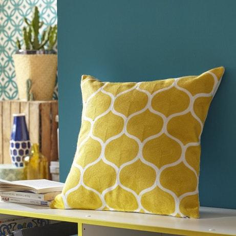 Un coussin jaune et blanc à formes géométriques