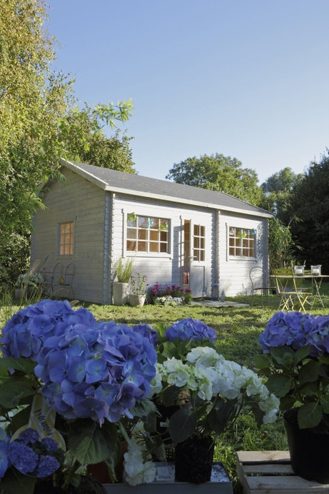 Un abri de jardin en bois blanc